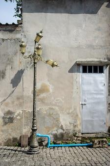 Lâmpada de rua velha e quebrada com porta do muro de cimento e do metal no fundo.