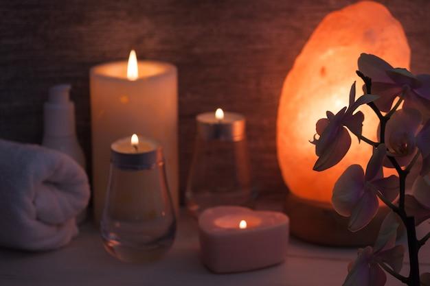 Lâmpada de sal do himalaia com flor de orquídea, óleo, toalha, velas no quarto escuro.