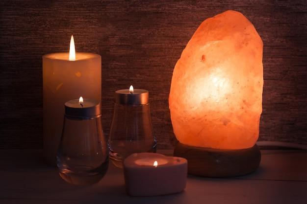 Lâmpada de sal do himalaia com velas no quarto escuro. spa, relaxe o conceito.