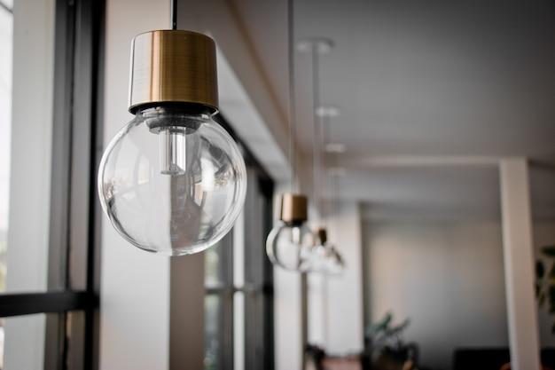 Lâmpada de suspensão perto da janela de vidro