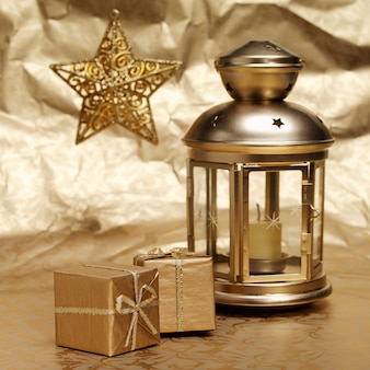 Lâmpada de velas, presentes e estrelas em fundo de papel dourado amassado