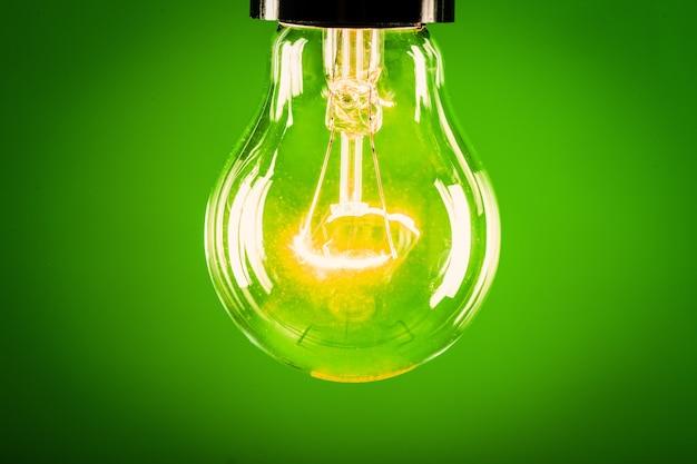 Lâmpada de vidro brilhante sobre fundo verde