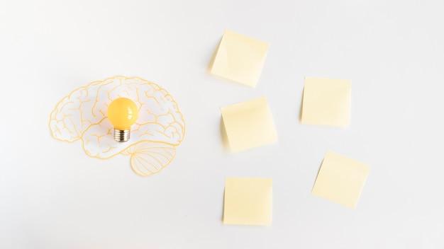 Lâmpada dentro do cérebro perto de notas adesivas
