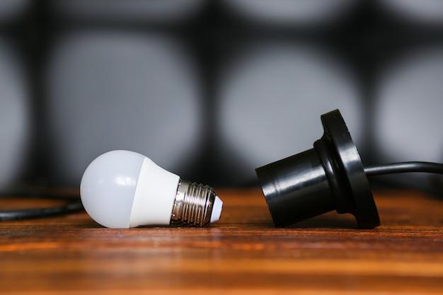 Lâmpada desaparafusada perto de um cartucho para uma lâmpada. falta, queda de energia. a eletricidade não é fornecida para a casa, apartamento. foto de alta qualidade