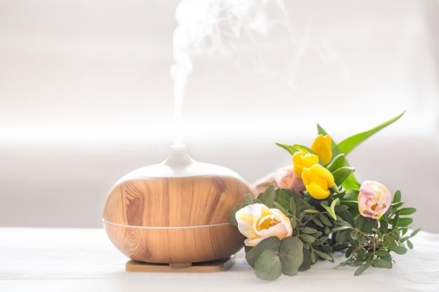 Lâmpada difusor de óleo de aroma em cima da mesa em um fundo desfocado com um lindo buquê de tulipas primavera.
