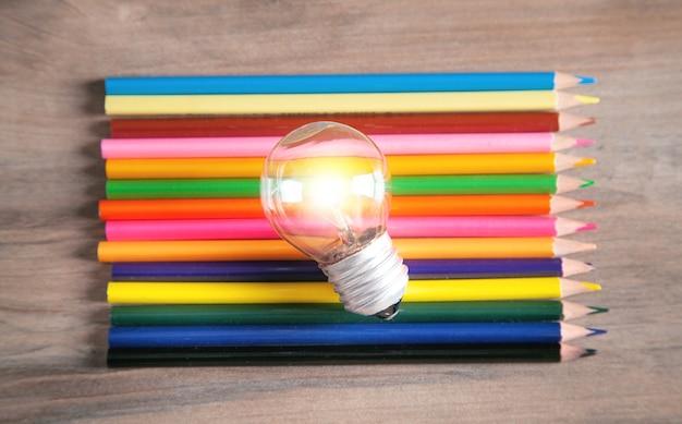 Lâmpada e lápis coloridos no fundo de madeira.
