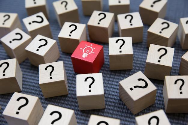 Lâmpada e ponto de interrogação ícones em blocos de madeira.