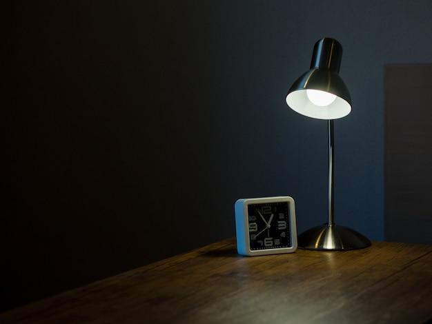 Lâmpada e relógio no quarto escuro com o conceito de luz e sombra