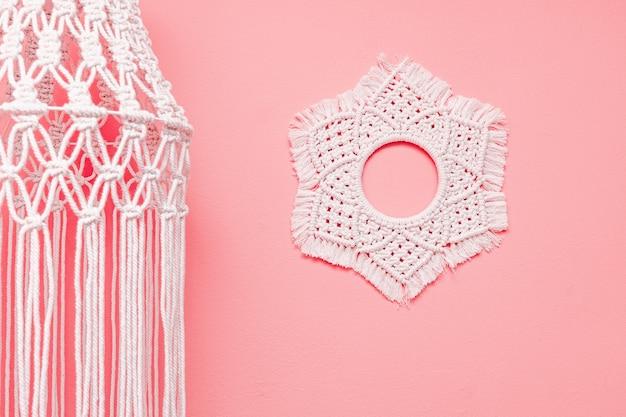 Lâmpada e tapeçaria de macramê penduradas no fundo rosa da parede
