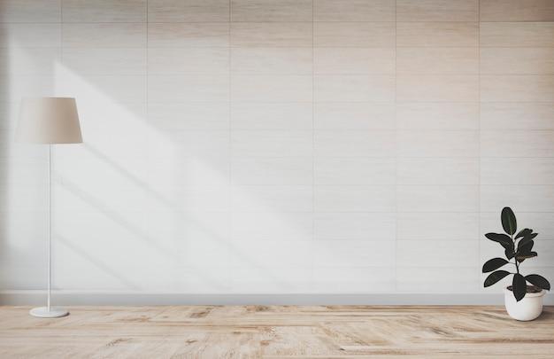 Lâmpada e uma planta na parede de uma sala vazia