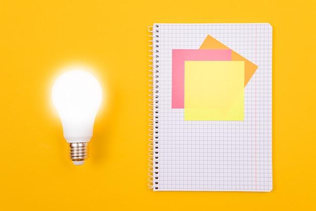 Lâmpada economizadora brilhante e um bloco de notas com notas adesivas