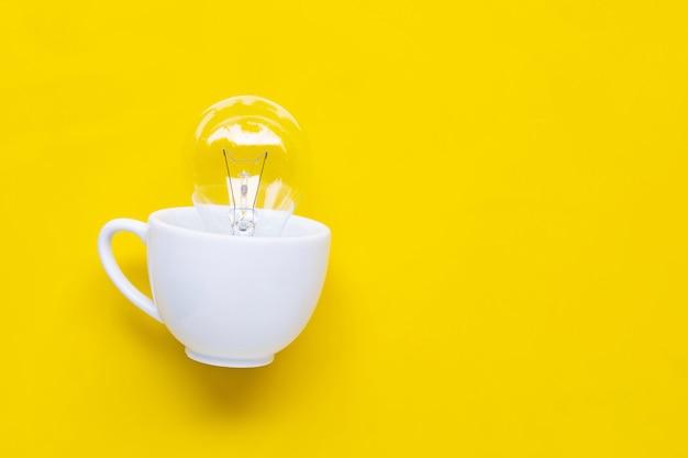 Lâmpada em copo branco sobre fundo amarelo.