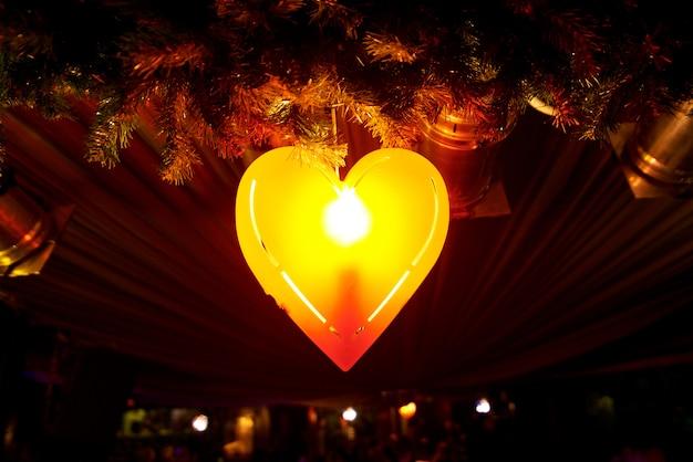Lâmpada em forma de coração vermelho brilhante sobre um fundo preto