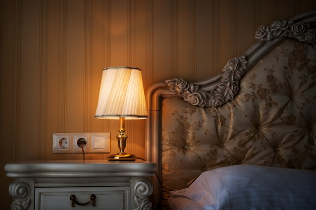 Lâmpada em uma mesa de cabeceira ao lado de uma cama
