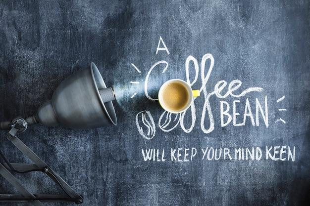 Lâmpada iluminada sobre a xícara de café e texto no quadro-negro