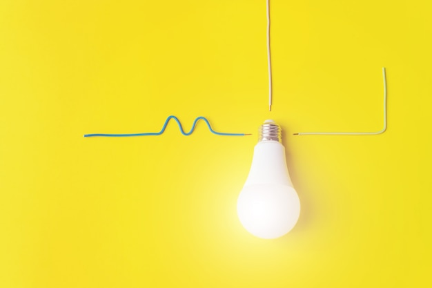 Lâmpada incandescente branca contra fundo amarelo com fase de fios, zero, aterramento. ideia, inovação