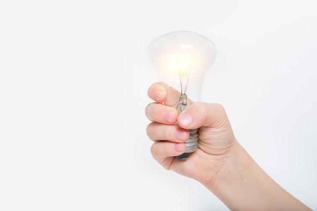 Lâmpada incandescente brilhante na mão de uma criança em um fundo claro