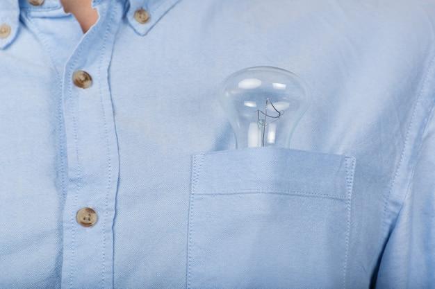 Lâmpada incandescente no bolso da camisa de um homem. fechar-se