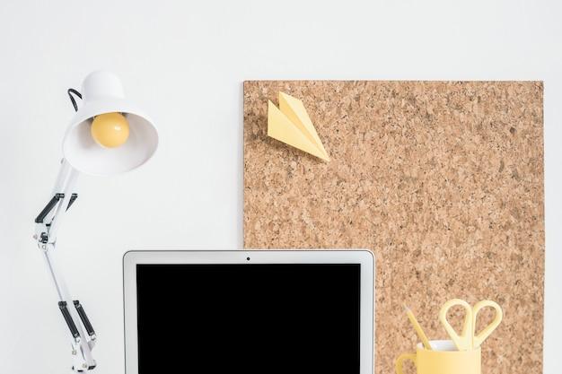 Lâmpada, laptop e placa de cortiça contra parede branca