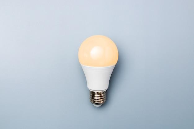 Lâmpada led com luz laranja contra um fundo cinza com espaço de cópia. conceito de eficiência energética