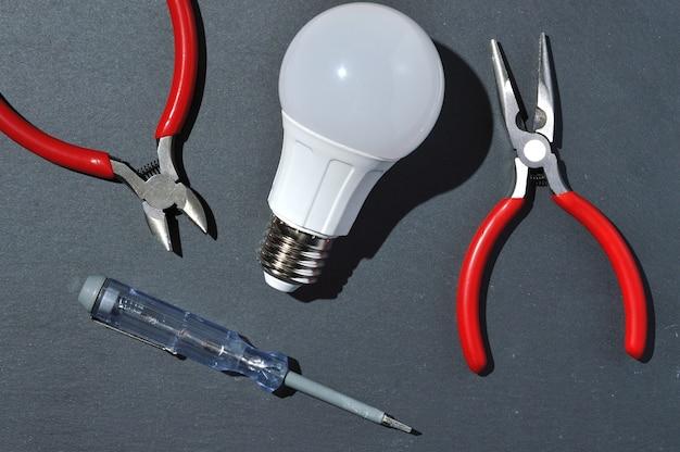 Lâmpada led e ferramentas para (alicate e testador de chave de fenda.) em um fundo preto. vista de cima.
