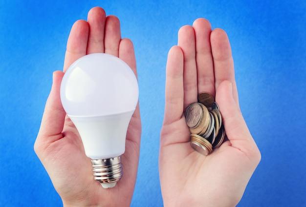 Lâmpada led e uma pilha de moedas nas mãos, palmas das mãos em um background azul