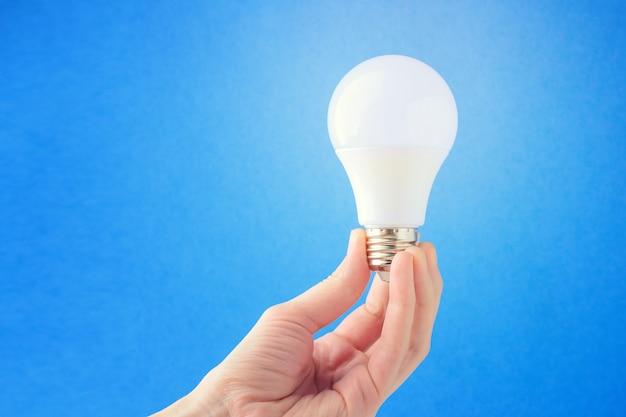 Lâmpada led na mão sobre um fundo azul. conceito da ideia