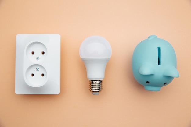 Lâmpada led, tomada e cofrinho azul. economia de energia de potência. vista do topo.