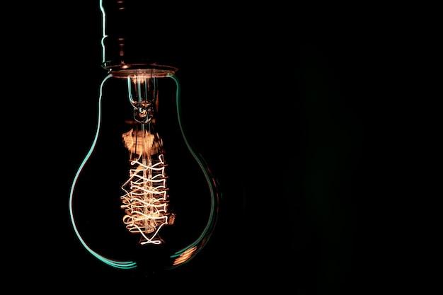 Lâmpada luminosa pendurada no escuro. conceito de decoração e ambiente.
