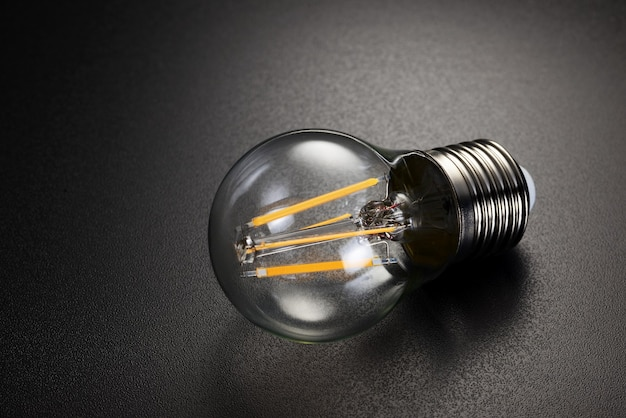 Lâmpada moderna de filamento de led transparente em fundo preto.