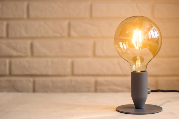 Lâmpada moderna minimalista amarela no interior no fundo de uma parede de tijolos na área de trabalho
