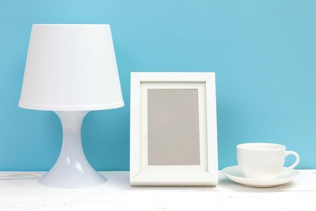 Lâmpada, moldura e xícara de café na mesa de madeira