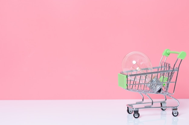 Lâmpada no carrinho de compras em fundo rosa com espaço de cópia. conceito de ideia e inspiração.