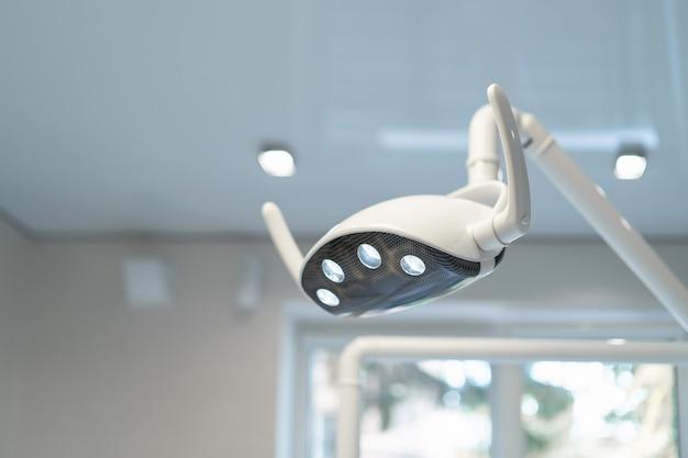 Lâmpada odontológica modenrt com luz acesa no consultório odontológico