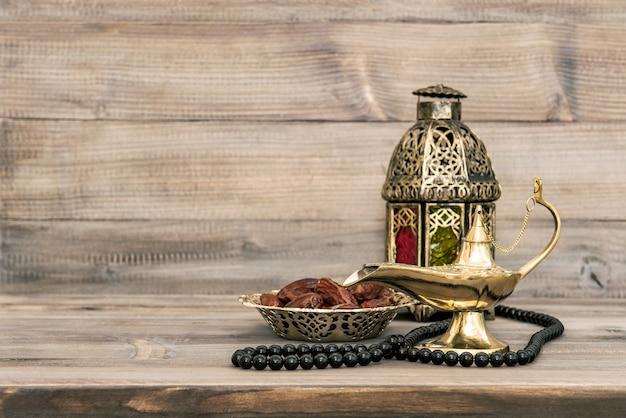 Lâmpada oriental e datas na mesa de madeira. natureza morta festiva com rosário