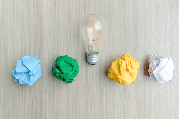 Lâmpada ou lâmpada com papel amassado colorido na mesa de madeira