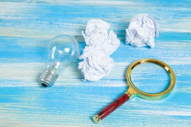 Lâmpada, papéis amassados e uma lupa. pesquisa de conceito por ideias no lixo com fundo de madeira