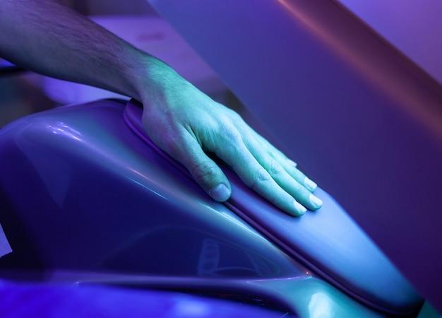 Lâmpada para bronzeamento, detalhe da mão.