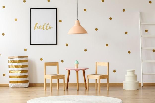 Lâmpada pastel acima da mesa e cadeiras de madeira no interior do quarto infantil branco e dourado com pôster. foto real