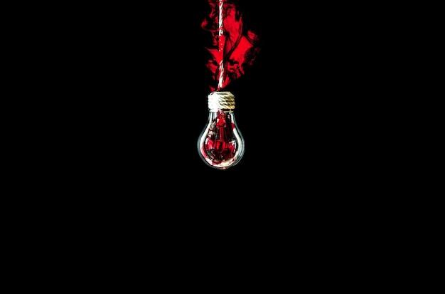 Lâmpada pendurada na corda. fogo vermelho lá dentro. novo conceito de ideia. isolado em um fundo preto.