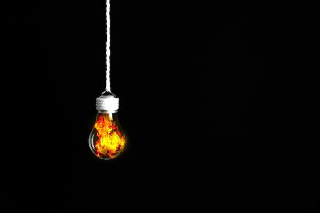 Lâmpada pendurada na corda. isolado em fundo preto. fogo por dentro. novo conceito de ideia.