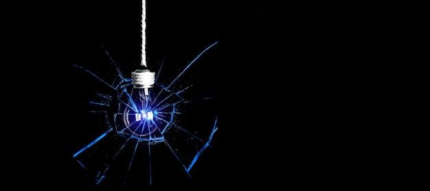 Lâmpada pendurada na corda. isolado em um fundo preto. novo conceito de ideia. vidro quebrado.