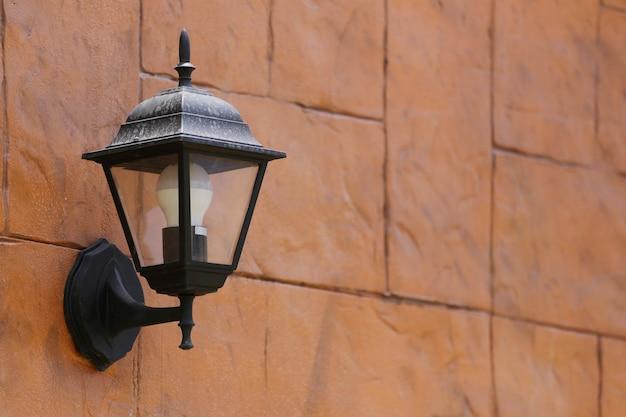 Lâmpada preta moderna que pendura da parede de tijolo de brown.