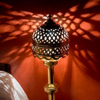 Lâmpada tradicional iluminada em um quarto no hotel la sultana, marrakech, marrocos