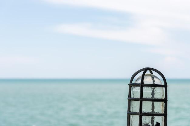 Lâmpada velha do vintage com a opinião do mar.