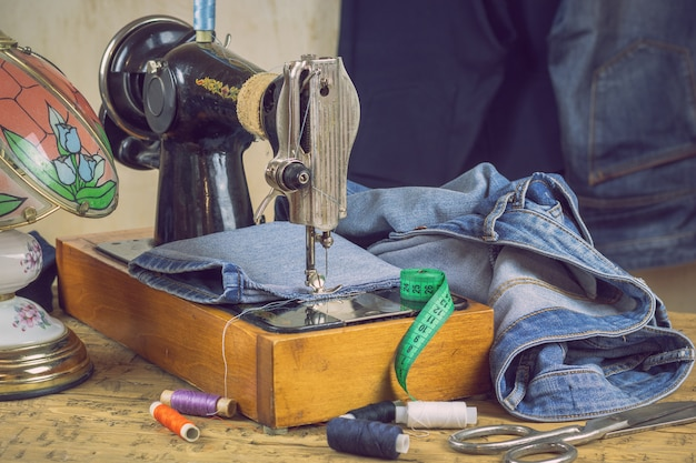 Lâmpada vintage e máquina de costura com jeans.