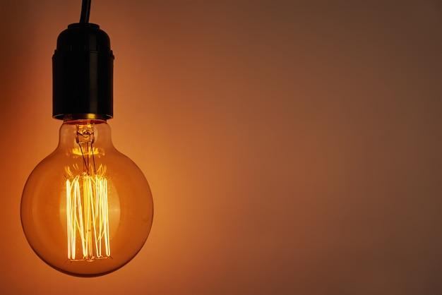 Lâmpada vintage em fundo laranja com espaço de cópia. lâmpada edison brilhante