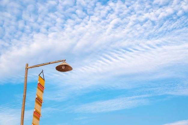 Lâmpada vintage no topo do poste de bambu e bandeira amarela lanna