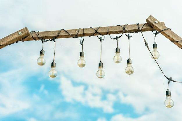 Lâmpadas acesas em uma viga de madeira contra um fundo de céu azul. bela decoração i