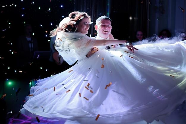 Lâmpadas brilham como estrelas sobre o casal de noivos girando na pista de dança